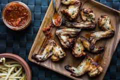 Asas de galinha em uma placa de madeira com batatas e molho de tomate Foto de Stock Royalty Free