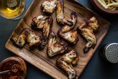 Asas de galinha em uma placa de madeira com molho das batatas, da bebida e de tomate Imagem de Stock Royalty Free