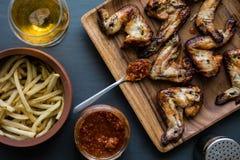 Asas de galinha em uma placa de madeira com molho das batatas, da bebida e de tomate Fotos de Stock