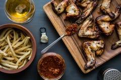 Asas de galinha em uma placa de madeira com molho das batatas, da bebida e de tomate Imagens de Stock Royalty Free
