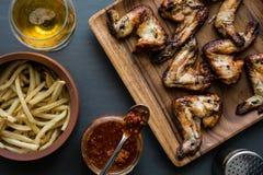 Asas de galinha em uma placa de madeira com molho das batatas, da bebida e de tomate Fotografia de Stock