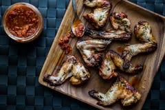 Asas de galinha em uma placa de madeira com molho de tomate Fotos de Stock