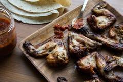 Asas de galinha em uma placa de madeira com molho e lavash Fotografia de Stock