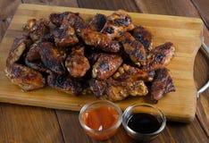 Asas de galinha grelhadas na madeira Fotografia de Stock Royalty Free
