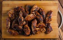 Asas de galinha grelhadas na madeira Fotos de Stock