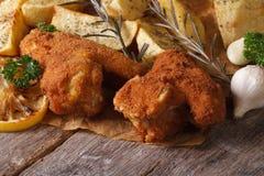 Asas de galinha mergulhadas na massa com batatas perto acima Fotografia de Stock Royalty Free
