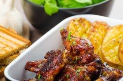 Asas de galinha pegajosas com pão do panini do alho fotos de stock