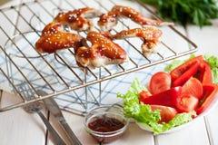Asas de galinha picantes quentes do BBQ na grade com molho Imagem de Stock