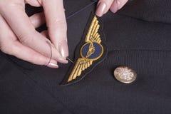 Asas dos pilotos que estão sendo costuradas no uniforme Fotografia de Stock Royalty Free