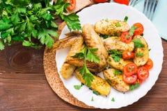 Asas e batatas cozidas de galinha, tomates frescos e verdes Foto de Stock Royalty Free