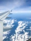 Asas e nuvens do avião no céu azul imagens de stock royalty free