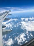 Asas e nuvens do avião no céu azul foto de stock