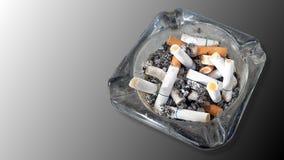 Asbakje en uitgestoken die uit sigaretten op gradiënt grijze bac wordt geïsoleerd Royalty-vrije Stock Fotografie