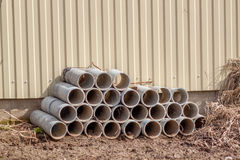 Asbestos-cement pipe. Gray construction pipe lying on the ground near the yellow fence. Building materials. Pipe used to protect wires from hostile environments Royalty Free Stock Images