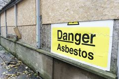 Asbestos danger sign at building construction site refurbishment of old building. Uk royalty free stock photography