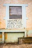 Asbestos hazard. Warning of asbestos danger on wall of abandoned factory stock photography