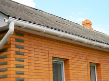 Asbestos roof with plastic rain gutter Stock Photo