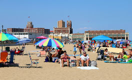 Asbury Park Beach. People enjoying a beautiful summer day at the Beach in Asbury Park, NJ. In the background the Convention Hall Building Stock Image