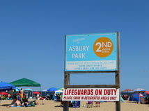 Asbury Park Beach Sign. In the entrance to the beach.In the background people on the beach with umbrellas. Asbury Park, NJ Royalty Free Stock Photos