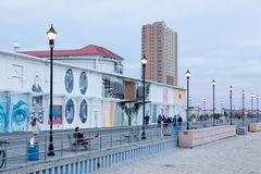 Asbury Park Boardwalk During Summer at Sunset. ASBURY PARK, NEW JERSEY - July 24, 2017: People walk on the boardwalk near Convention Hall at sunset Stock Image