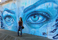 Asbury Park Boardwalk Mural. A young Woman posing for a photo in front of the mural, Mermaid Eyes, by artist Thiago Valdi. This artwork is one of twelve murals Royalty Free Stock Image