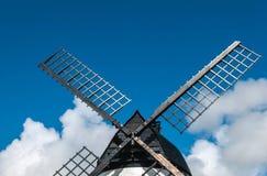 Ascendente próximo do moinho de vento, com velas pretas e o céu azul Foto de Stock