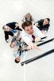 Ascending the ladder. Above view of businessman ascending the ladder with his crew beneath Stock Image