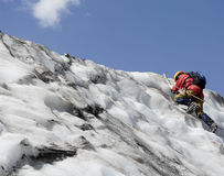 Ascending mountaineer. Mountaineer makes his way up to the top royalty free stock photos