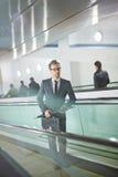 Ascending. Serious businessman with briefcase and umbrella ascending on escalator Stock Photos