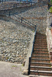 Ascending stone steps on a cobble wall Stock Image