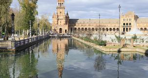 Ascending view of northern tower  on Plaza de Espana. Ascending view of northern tower reflecting in water on Plaza de Espana in Seville, Spain stock footage