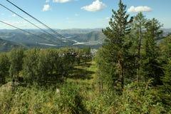 Ascenseur de chaise à la montagne entre les arbres au-dessus de la forêt Photo libre de droits