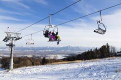 Ascenseur de chaise avec des skieurs les montagnes de fond slovakia Photo stock