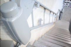 Ascenseur de chaise pour les personnes âgées handicapées et aux escaliers de bibliothèque image stock