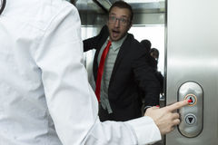 Ascenseur de pressing de femme d'affaires vers le haut de bouton Essai confus par homme d'affaires d'arrêter l'ascenseur photographie stock
