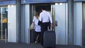 Ascenseur entrant de jeunes couples à l'aéroport, au voyage d'affaires, au voyage et au tourisme Images libres de droits