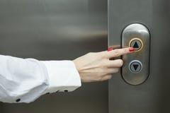 Ascenseur femelle de pressing de main vers le haut de bouton photographie stock libre de droits
