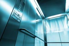 Ascenseur intérieur en métal et en verre en bâtiment moderne, boutons brillants et balustrades Images libres de droits