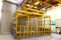 Ascenseur jaune dans le quai de chargement pour charger la machine lourde à l'intérieur du buil Photographie stock libre de droits
