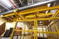 Ascenseur jaune dans le quai de chargement pour charger la machine lourde à l'intérieur du buil Photo stock