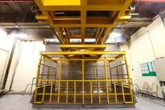 Ascenseur jaune dans le quai de chargement pour charger la machine lourde à l'intérieur du buil Image stock