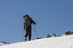 Ascensión de los hombres perfilada en un cielo azul durante viajar del esquí Imagen de archivo libre de regalías