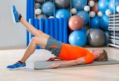 Ascensore dell'anca con l'esercizio biondo della palestra dell'uomo di estensione della gamba Fotografie Stock Libere da Diritti