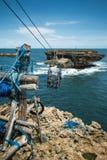 Ascensore della cabina di funivia fra la costa della spiaggia di Timang e la piccola isola rocciosa Immagine Stock