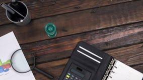 Ascensore della gru, tavola di lavoro di legno moderna dello scrittorio di vista superiore con il grafico e lente d'ingrandimento stock footage