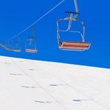 Ascensore di sci di inverno in montagne nevose contro cielo blu Fotografie Stock