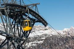 Ascensore di sci giallo della cabina di funivia che va su sulla cima della montagna Immagine Stock Libera da Diritti