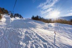 Ascensore di sci in montagna con i percorsi dai cieli e dagli snowboard Immagini Stock