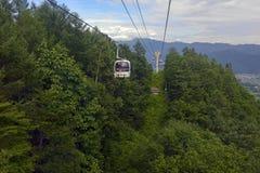 Ascensore di sci nelle montagne che portano i passeggeri alla traccia di escursione Immagini Stock