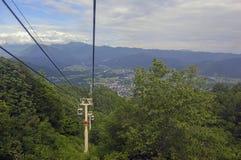 Ascensore di sci nelle montagne che portano i passeggeri alla traccia di escursione Fotografia Stock